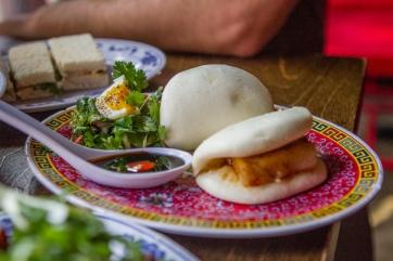 still life with pork bun, tea sandwiches, and elbow